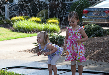 Young girls playing in a sidewalk sprinkler, in the North Main neigbhorhood