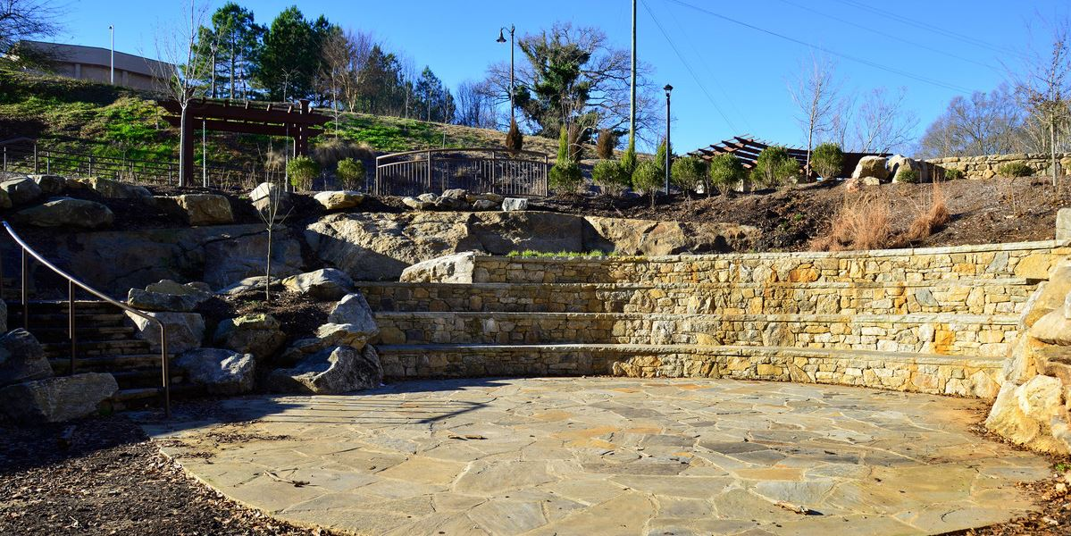 A small outdoor amphitheater is located next to the Reedy River