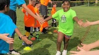 Photo of young soccer player getting high fives from teammates