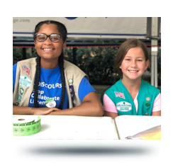 Two girl scouts selling tickets at a local event