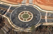 Aerial view of a roundabout with 3 merging areas of traffic and all of the signals painted on the ro