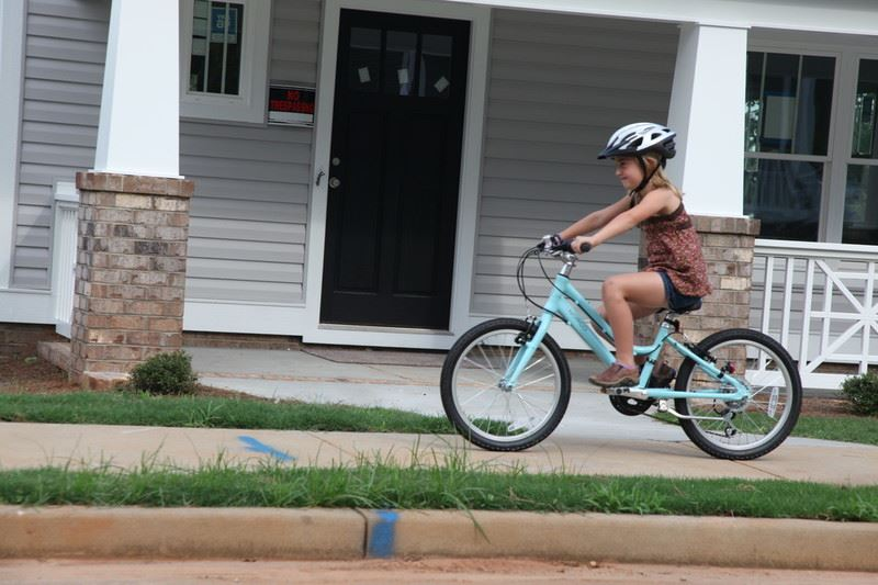 Child riding bicycle through a Greenville neighborhood